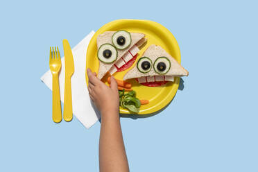 Hand of baby girl picking up funny looking sandwich withanthropomorphic face - GEMF04130