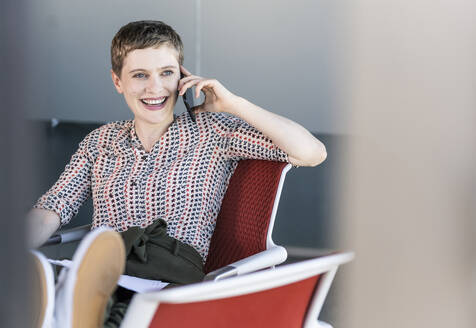 Happy businesswoman sitting on office chair talking on the phone - UUF21085