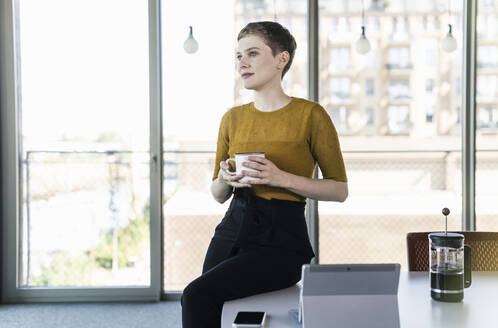 Businesswoman sitting on desk in office holding coffee mug - UUF21130