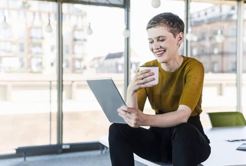 Businesswoman sitting on desk in office using tablet - UUF21148