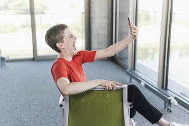 Carefree businesswoman using smartphone in office - UUF21160