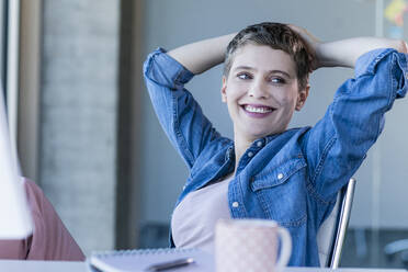 Smiling relaxed businesswoman sitting at desk in office - UUF21172