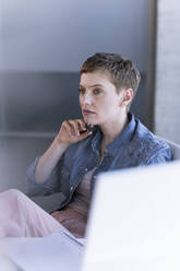 Businesswoman thinking at desk in office - UUF21178