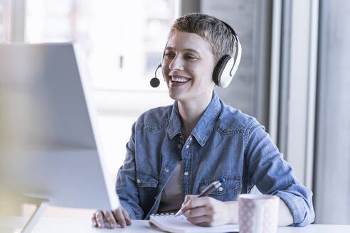 Smiling businesswoman wearing headset at desk in office taking notes - UUF21181
