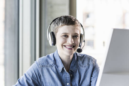 Portrait of smiling businesswoman wearing headset at desk in office - UUF21184