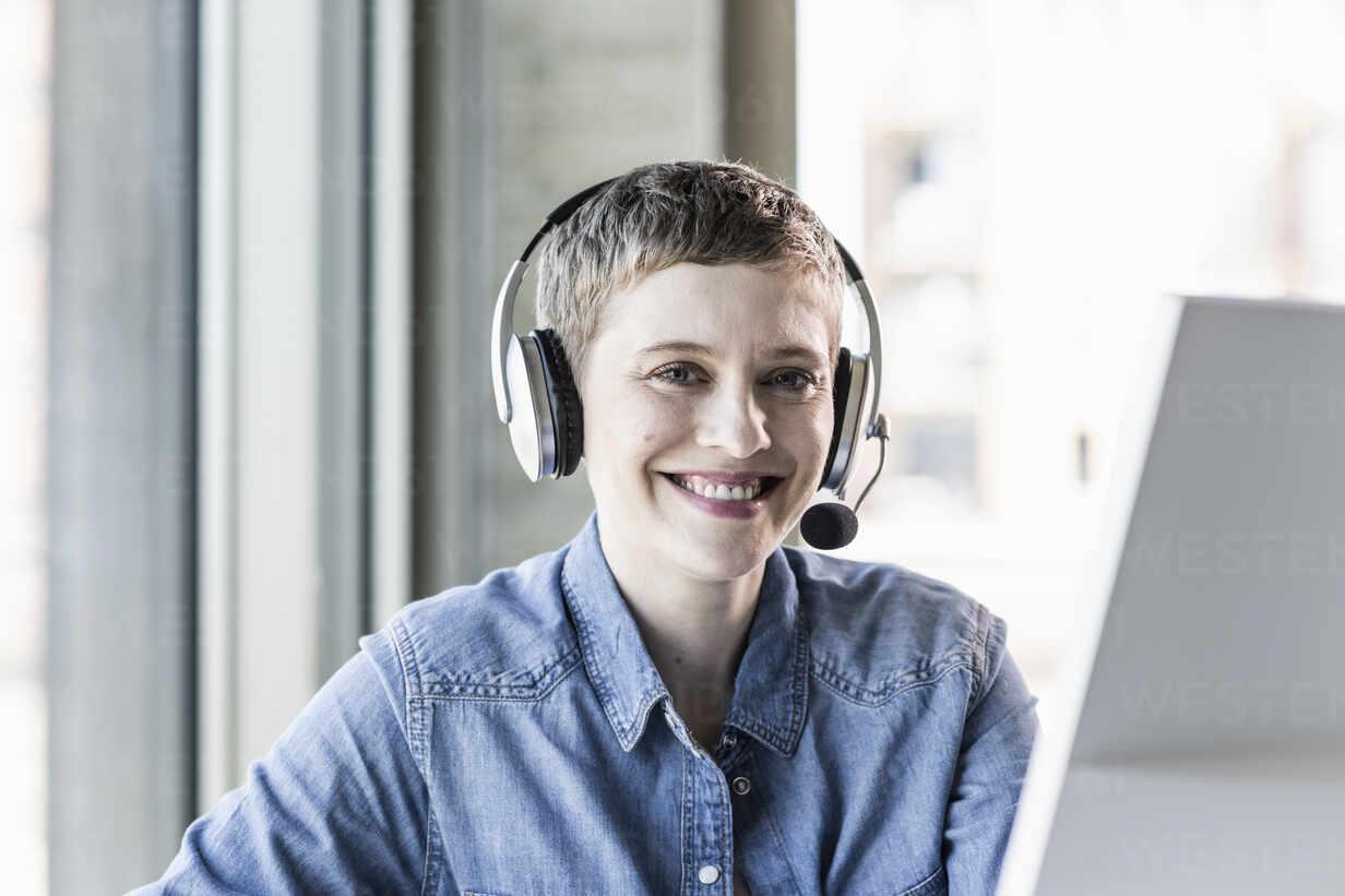 Portrait of smiling businesswoman wearing headset at desk in office - UUF21184 - Uwe Umstätter/Westend61