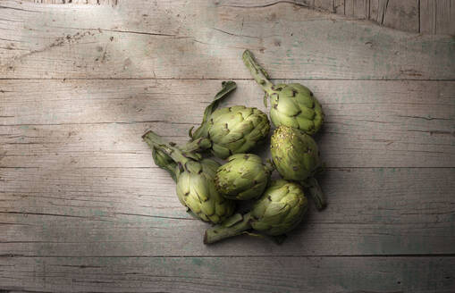 Fresh artichoke on old cracked wooden surface indoors - ADSF14594