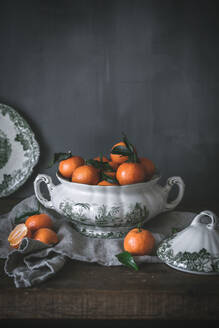 Sophisticated still life with ripe orange tangerines with green leaves in deep white bowl on table on gray background - ADSF14696
