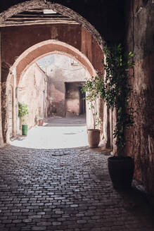 Paved path going through weathered archway on sunny day on street of Marrakesh, Morocco - ADSF14714