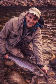 Smiling fly fisherman holding caught salmon fish in river - DHEF00356