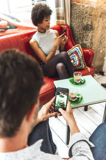 Man photographing coffee served on table while girlfriend using smart phone in cafe - EHF00788