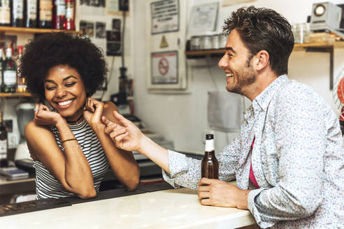 Man touching cheerful female bartender while flirting with her at bar counter - EHF00845