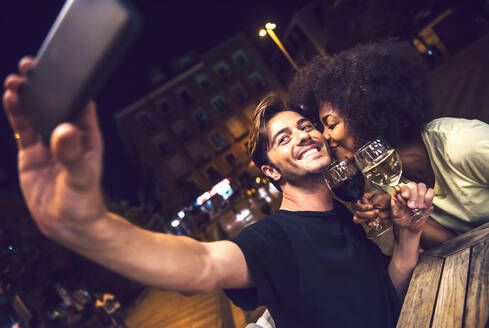 Woman kissing boyfriend taking selfie at date night - EHF00853