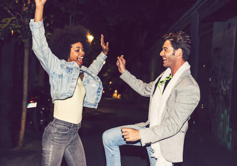 Cheerful couple dancing on street at night - EHF00868