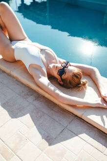 High angle of calm female in swimwear and sunglasses lying on edge of pool and sunbathing while looking at camera during vacation - ADSF14775