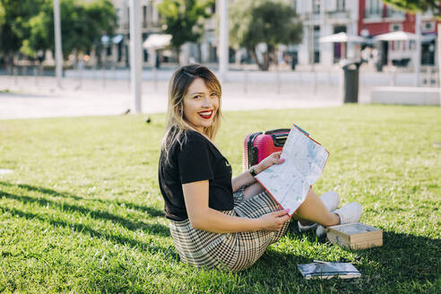 Happy beautiful woman with map sitting on grassy land in park - DCRF00778