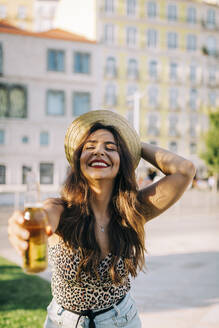 Cheerful young woman wearing hat holding beer bottle while standing in city - DCRF00787
