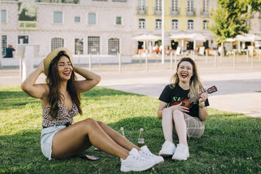 Carefree woman playing ukulele while sitting with friend on grassy land - DCRF00793