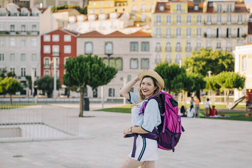 Beautiful woman with backpack wearing hat while standing on footpath in city - DCRF00799