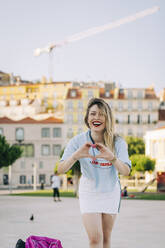 Cheerful young woman making heart shape while standing in city - DCRF00802