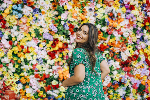 Smiling beautiful woman standing against colorful flowers - DCRF00808