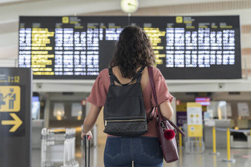 Young woman checking her flight in time board at airport - MTBF00660