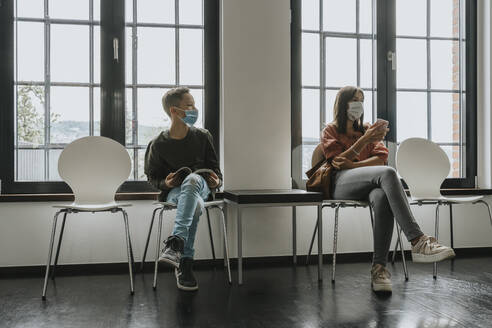 Teenage girl and boy wearing masks while sitting on chairs in waiting room - MFF06117