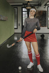 Smiling girl with hockey stick and ball standing on floor in health club - MFF06168