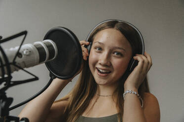 Close-up portrait of happy teenage girl singing against wall in recording studio - MFF06171