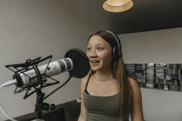 Teenage girl singing over microphone while standing against wall in recording studio - MFF06174