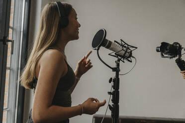 Teenage girl wearing headphones singing over microphone in studio - MFF06177