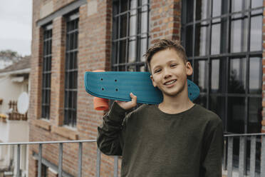 Smiling boy posing with blue skateboard while standing against building - MFF06183