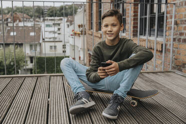 Smiling boy using smart phone while sitting on skateboard against railing - MFF06189