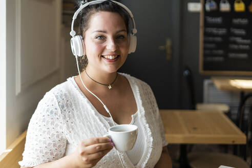 Close-up of smiling young woman holding coffee cup listening music through headphones in cafe - GIOF08792