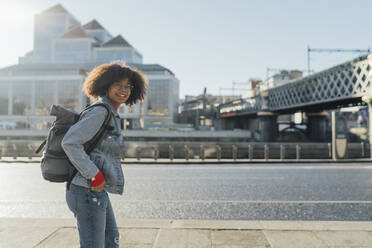 Smiling young woman with backpack standing on footpath by river in city - BOYF01444