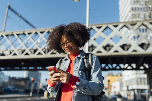 Smiling afro young woman using smart phone while standing against bridge in city - BOYF01450
