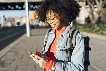 Close-up of smiling young woman with curly hair using mobile phone while standing on sidewalk  - BOYF01453