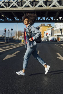 Cheerful young woman with afro hair running on street in city during sunny day - BOYF01459