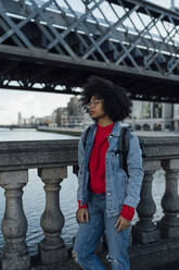 Thoughtful young woman with afro hair standing on footbridge over river in city - BOYF01462