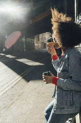 Afro young woman eating donut while standing on street during sunny day - BOYF01474