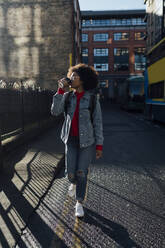Young woman drinking coffee while walking on street in city - BOYF01480