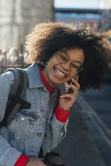 Close-up of cheerful afro woman talking over smart phone in city - BOYF01486