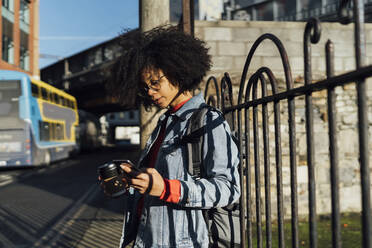 Young woman with curly hair using smart phone while standing by railing in city - BOYF01489