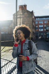 Cheerful afro woman talking over smart phone while standing with coffee cup on street - BOYF01492