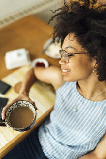 Close-up of young woman with eyes closed holding coffee cup while sitting at table - BOYF01504