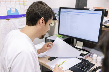Male doctor examining medical record while sitting at desk in hospital - DGOF01270