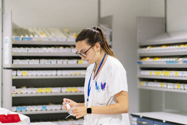 Female worker packing medicines while standing in pharmacy - DGOF01300