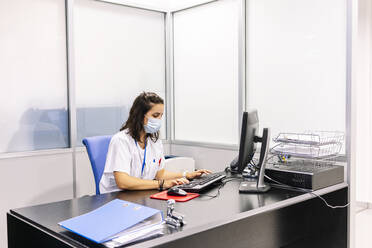 Female doctor wearing surgical mask using computer on desk in office at hospital - DGOF01324