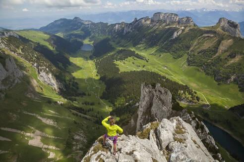 Rock climber on summit over valley, Alpstein, Appenzell, Switzerland - CAVF88754