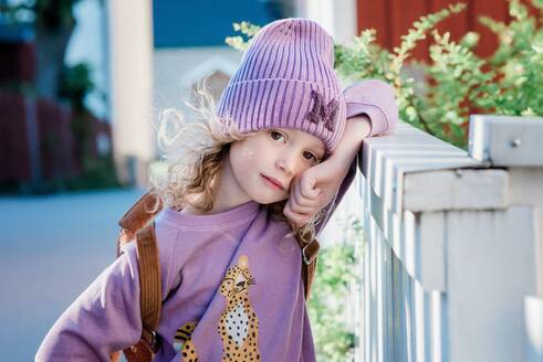 Portrait of a beautiful young girl leaning on a fence at school - CAVF88763